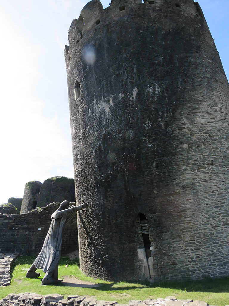 Wooden statue seemingly holding up a leaning castle tower