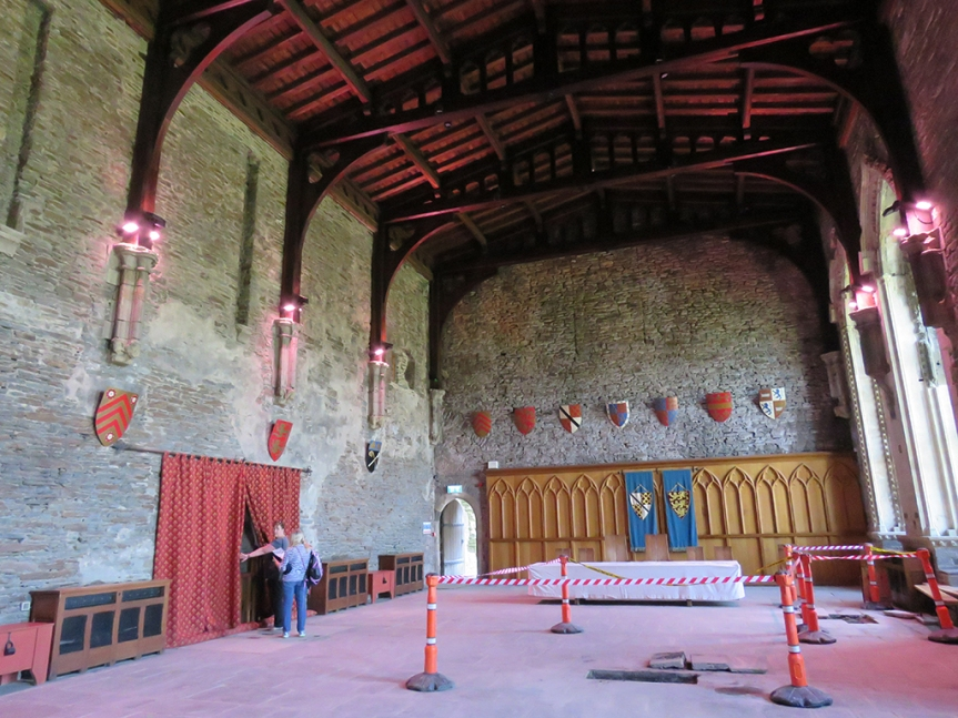 Large room with shields along the wall and vaulted wooden ceiling.