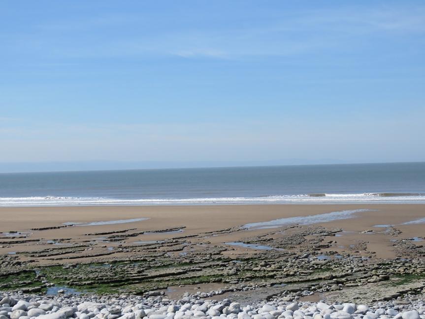 a broad rocky beach with sand toward the surf