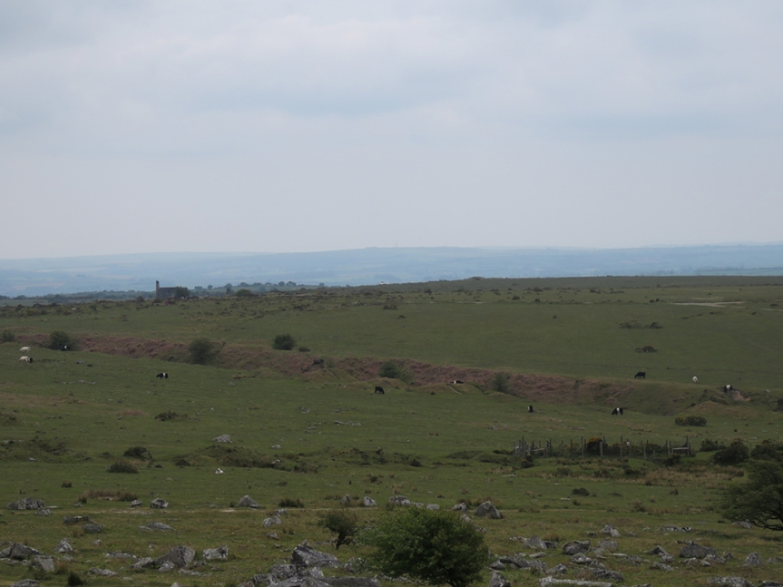 Pastureland and moorland with mist obscured hills in the background under a leaden sky.