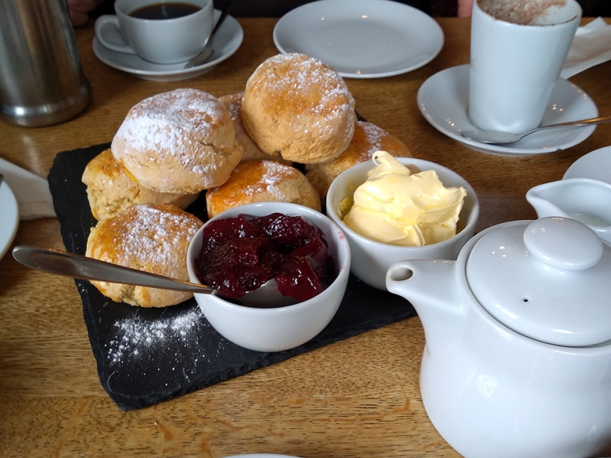 Tray of scones with bowls of clotted cream and jam. A teapot in the foreground.