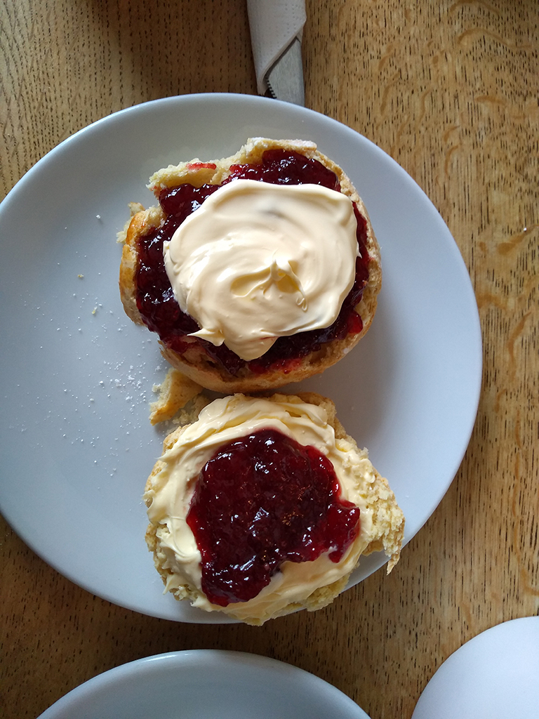 Two scones on a plate with cream and jam.