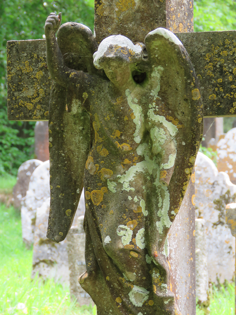 A lichen covered and eroded stone angel affixed to a stone cross headstone.