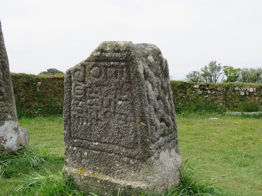 Ancient memorial stone with a Latin inscription. A stone wall is in the background.