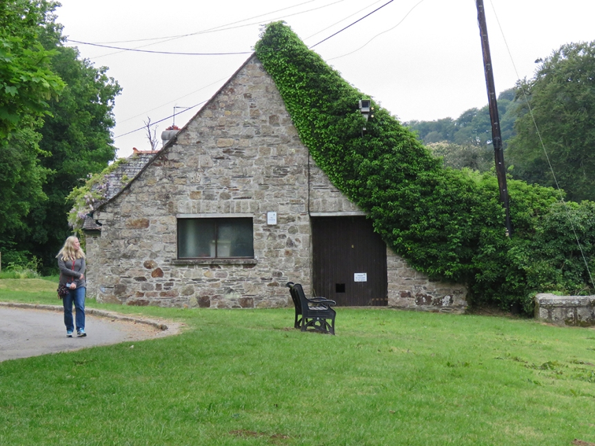 Stone building with ivy growing along one side, up the roof.