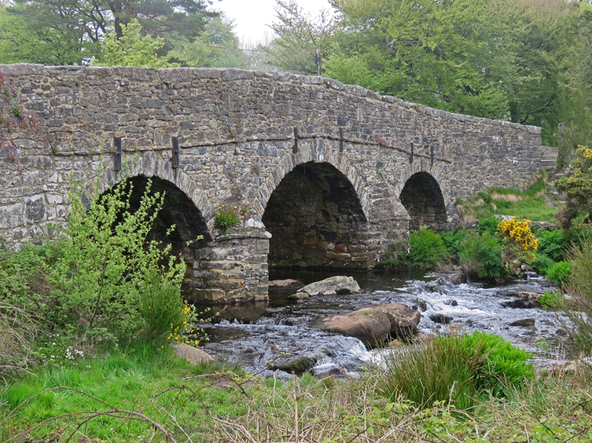 A stone bridge with three arches over a swiftly moving stream.