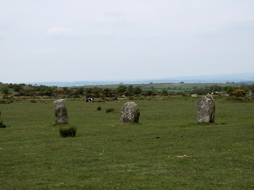 Three standing stones in a field with distant rolling hills in the background.