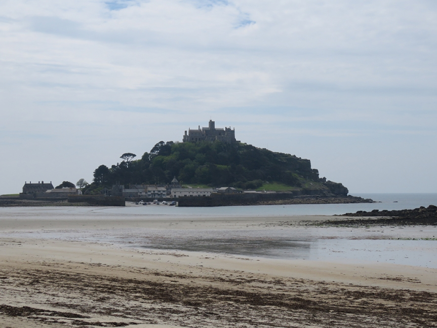 Castle atop a wooded island off the coast, a beach in the foreground.