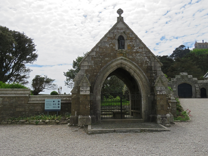 Stone archway with a metal gate at the end of a low stone wall.