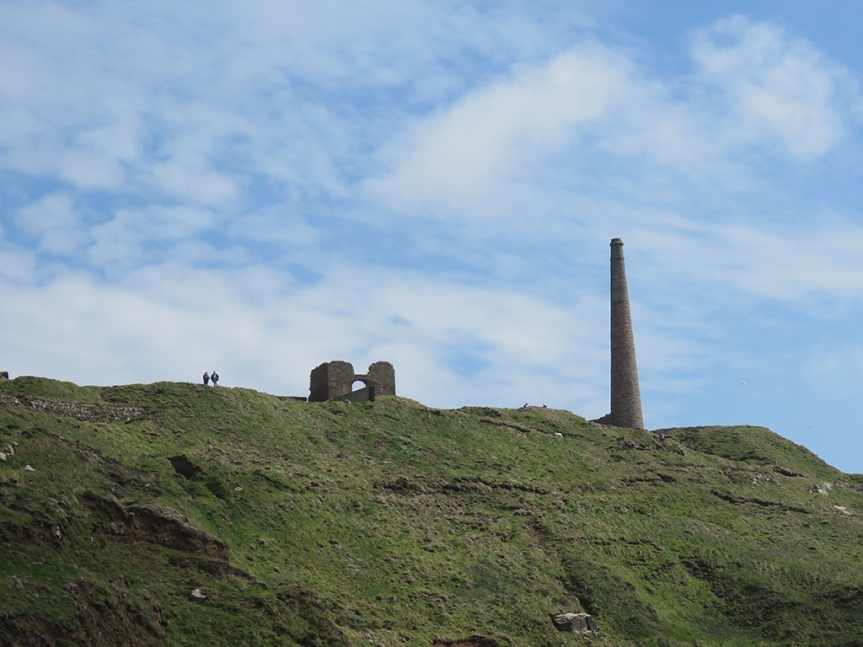 More stone ruins and a tall stone smokestack on a cliff top, with two people (looking quite small) standing nearby.