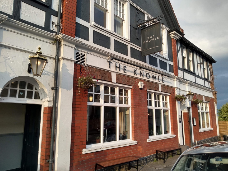 "Pub building, red brick and white trim. Sign says ""The Knowle""."