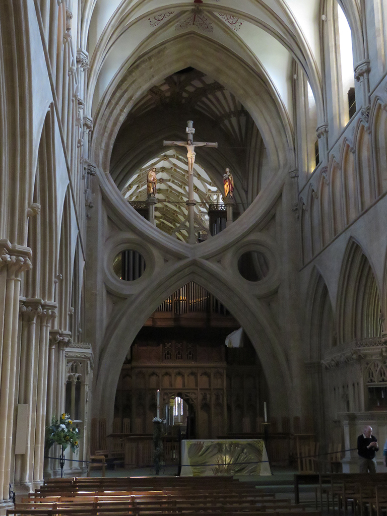 Gothic church interior with arches and a crucifix visible through the background.