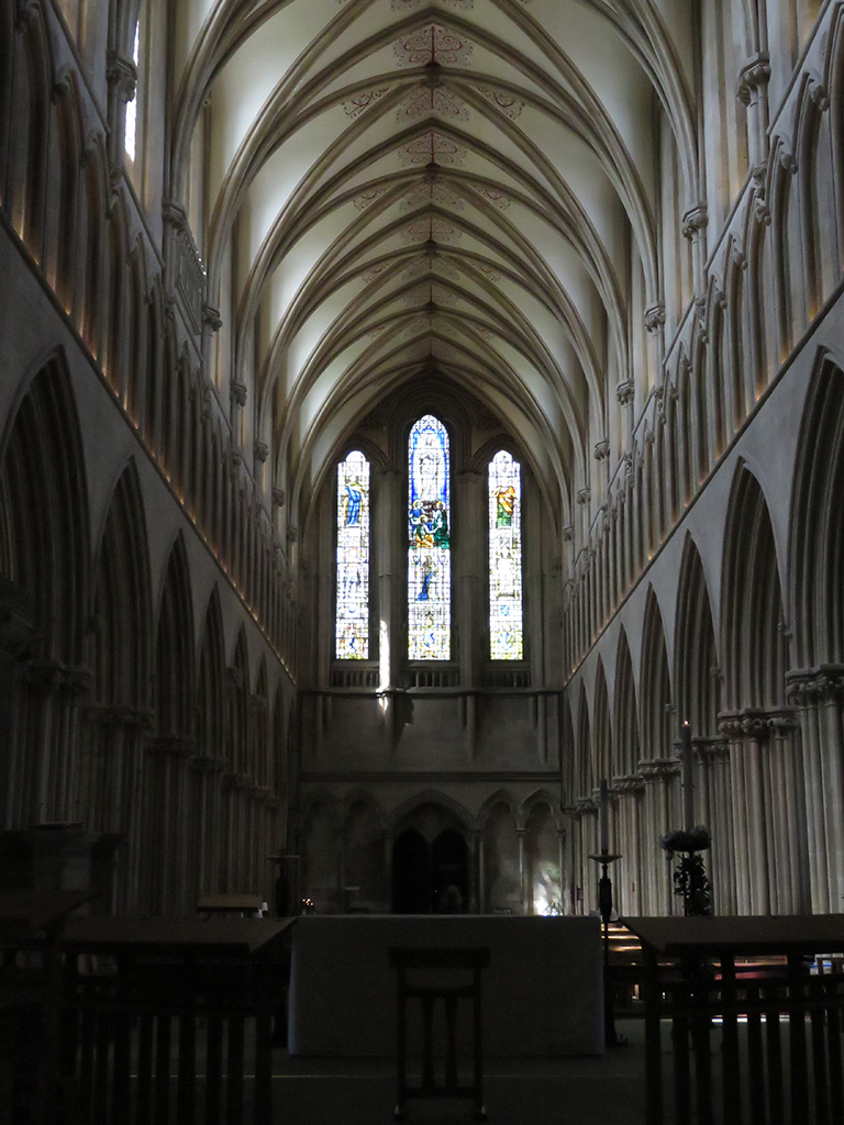 Interior view of a llarge church nave with stained-glass windows at the far end.