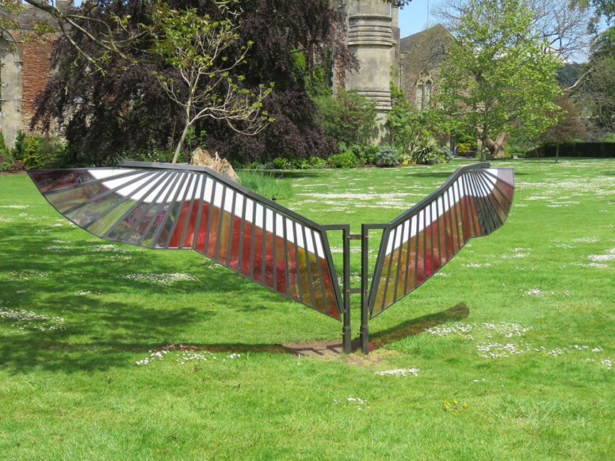 Colored glass sculpture shaped like bird wings.