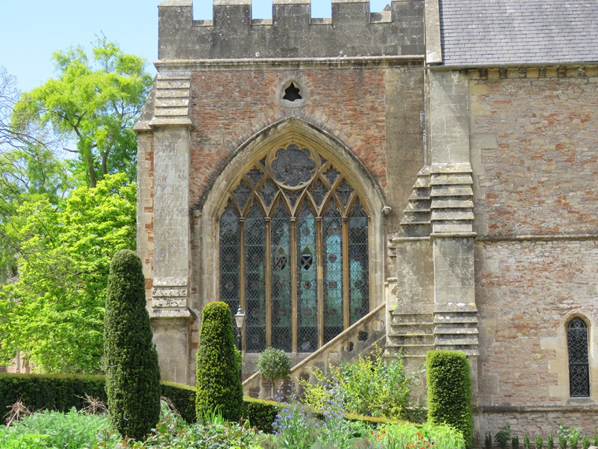 Stained glass arch window with topiaries in the foreground.
