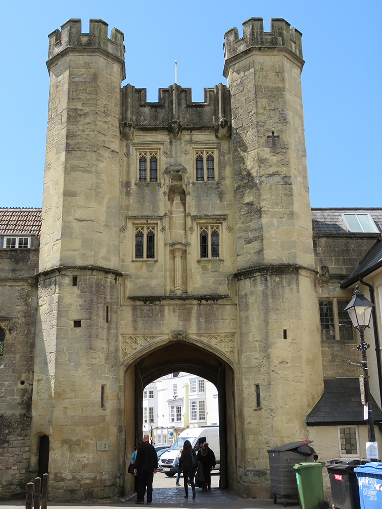 Ancient stone gatehouse with two turrets over a pointed arch entrance.