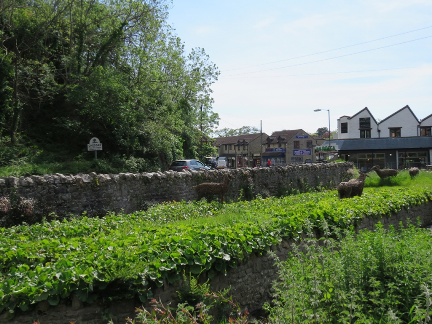 stone walls topped with herbaceous plants lead into a village.