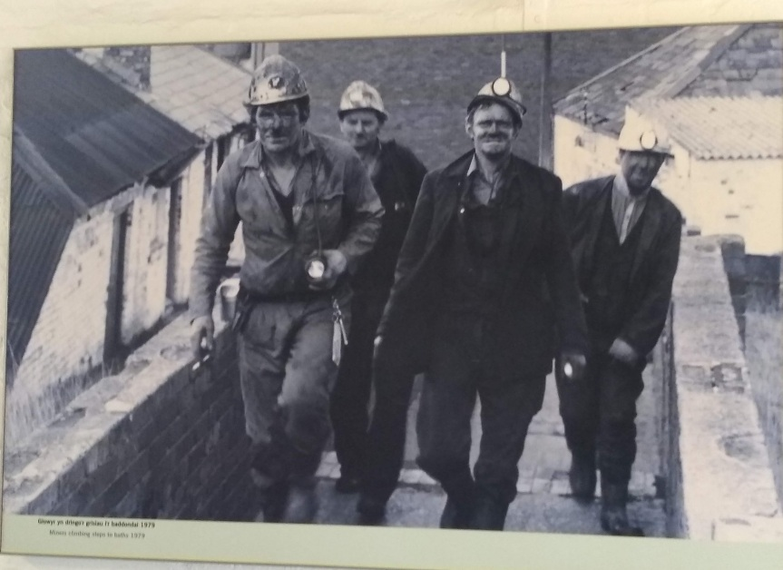 Photo display of Big Pit miners after their shift.
