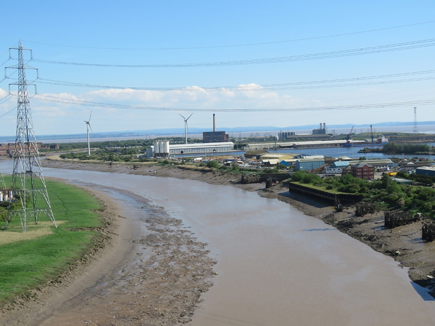 View of a muddy river and some industrial buildings in the distance.