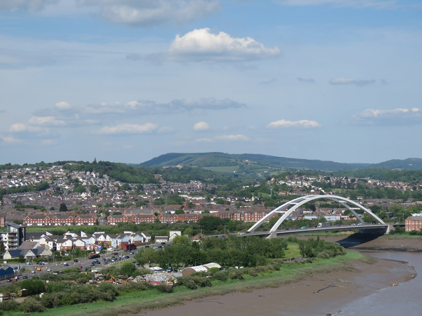 An arch bridge and buildings in the middle distance, a river in the foreground, and distant hills.